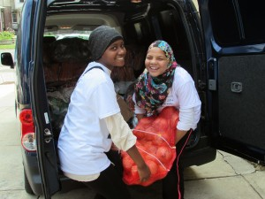 Amatullah Brown (l.), a 15-year-old Central High School student, joins her friend Noor Borwman (r.), a 13-year-old PA Cyber Charter School student, in hoisting some of the produce donations amassed by area Muslims as part of Ramadan.