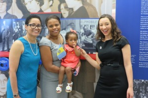 Members of the late Clarence Farmer Sr.'s family – niece, the Hon. Carolyn Nichols, granddaughter, Dr. Nicole Farmer Woodard, holding great-granddaughter, Morgan, and granddaughter, Helen Farmer, pose by his photo, one of those featured in Civil Rights in Philadelphia: 50th Anniversary of the Civil Rights Act of 1964 at the Philadelphia International Airport.