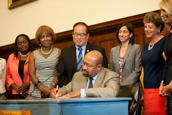 Mayor Michael A. Nutter enacts Bill No. 130922, ensuring breastfeeding accommodation in Philadelphia workplaces, witnessed by (l-r) Saniah R. Johnson, Councilwoman Blondell Reynolds Brown, Councilman David Oh, Rue Landau, Carol Fischer and Letizia Amadini Lane, vice president and global head, Employee Value Proposition, Office of CEO and Corporate Strategy, GSK. Photo courtesy Kait Pritivera.