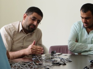 Imam Barzan Barn Rashid (l.) discusses fundraising efforts for widows, orphans and others displaced post-war in Iraq during a visit to PCHR.