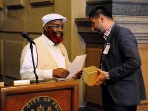 Commissioner Saadiq Jabbar Garner, subbing for Mayor Michael A. Nutter, offers Imam Barzan Barn Rashid a commemorative gift on behalf of the city – a replica Liberty Bell.