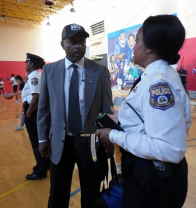 Lt. Kenora Scott looks over the action as Rev. George Clark, a referee, chats with 16th District Capt. Altovise Love-Craighead. In addition to offering those services, Clark also seeks to train young people to be referees.