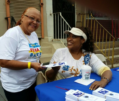 Sara Roblado, an area block captain, takes a moment to collect information from PCHR's Nancy Rivera at the annual Feria del Barrio.