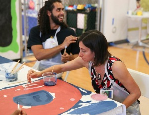PCHR Executive Director Rue Landau adds a stroke of brilliance to the Gloria Casarez mural.